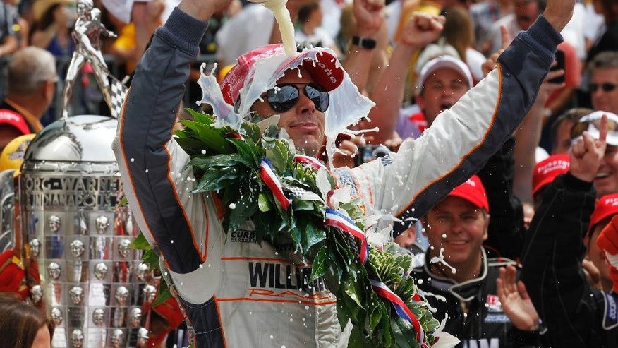 FILE - In this May 29, 2011, file photo, IndyCar driver Dan Wheldon, of England, douses himself with milk after winning the Indianapolis 500 auto race at the Indianapolis Motor Speedway in Indianapolis.   (AP Photo/Darron Cummings, File)