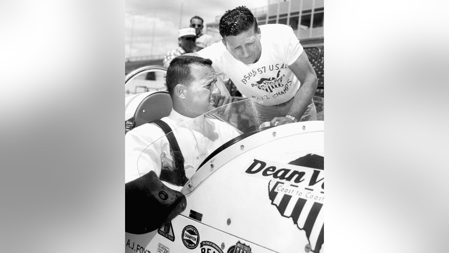 FILE - In this May 28, 1958, file photo, race car driver A.J. Foyt Jr., left, talks with his father, A.J. Foyt, at a pit stop during his afternoon practice runs at the Indianapolis Motor Speedway, in Indianapolis, Ind. Foyt won the Indy 500 auto race in 1961, 1964, 1967 and 1977. (AP Photo/File)