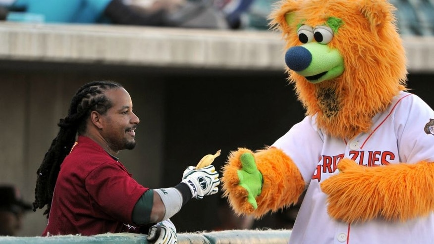 Parker has his eyes on a banana as Sacramento River Cats' Manny Ramirez smiles before the game against the Fresno Grizzlies, Monday, June 11, 2012, in Fresno, California. (John Walker/Fresno Bee/MCT)