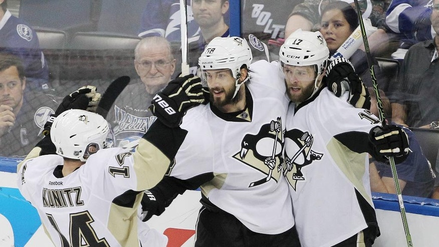 Pittsburgh Penguins defenseman Kris Letang (58) and left wing Chris Kunitz (14) celebrate Bryan Rust's (17) goal during the third period of Game 6 of the NHL hockey Stanley Cup Eastern Conference finals Tuesday, May 24, 2016, in Tampa, Fla. The Penguins defeated the Lightning 5-2. (AP Photo/Brian Blanco)