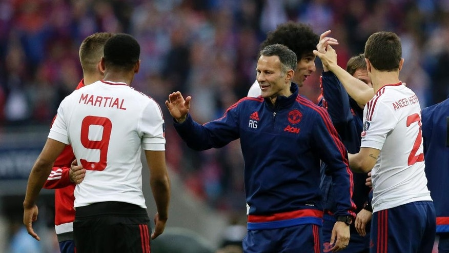 Manchester United assistant manager Ryan Giggs celebrates with player Anthony Martial after winning the English FA Cup final soccer match against Crystal Palace at Wembley Stadium, London on Saturday May 21, 2016. The final score was 1-2. (AP Photo/Tim Ireland)