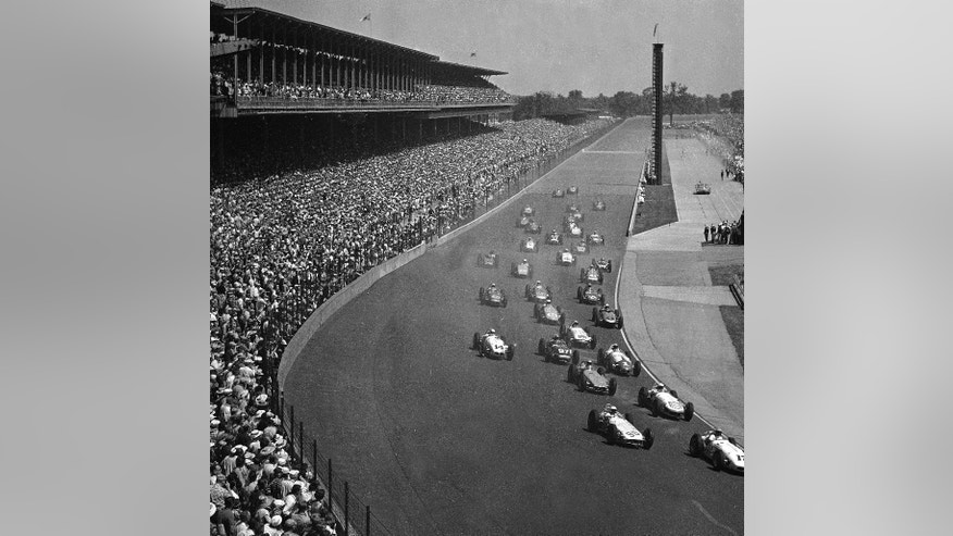 FILE - In this May 30, 1961, file photo, thirty-three cars at the Indianapolis Motor Speedway roar into the first turn as they start the Indy 500 auto race in Indianapolis. Eddie Sachs in the Dean Van Lines Special (12) is leading the pack. The 100th running of the Indy 500 is Sunday, May 29, 2016. (AP Photo/File)