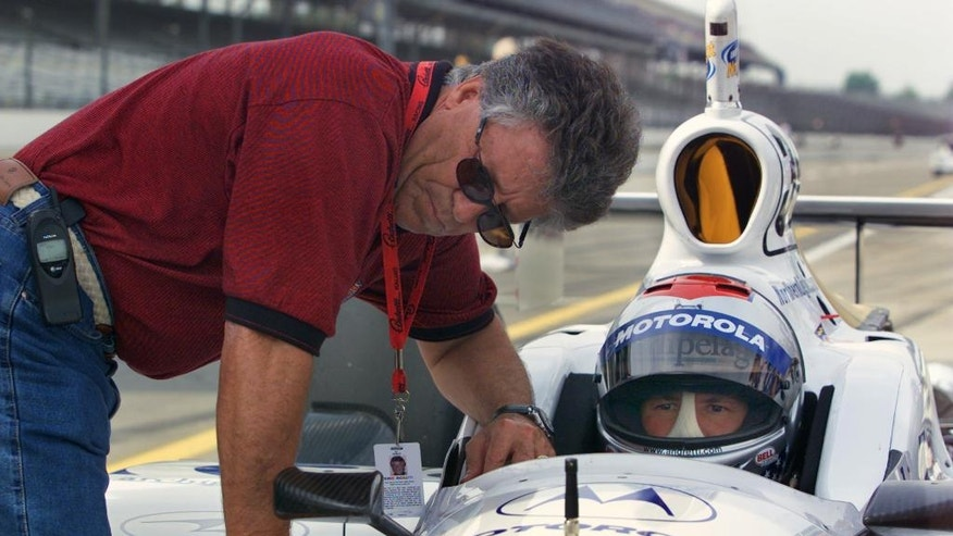 """FILE - In this May 10, 2001, file photo, Mario Andretti, left, chats with his son Michael during practice at Indianapolis Motor Speedway in Indianapolis. In the lead-up to the 100th running of the """"The Greatest Spectacle in Racing,"""" The Associated Press interviewed the 27 living race winners on topics ranging from the greatest driver to most memorable moment. Their answers to the best driver to never win the Indianapolis 500 gave Michael Andretti a distinction he'd rather go to anyone else.  (AP Photo/Michael Conroy, File)"""