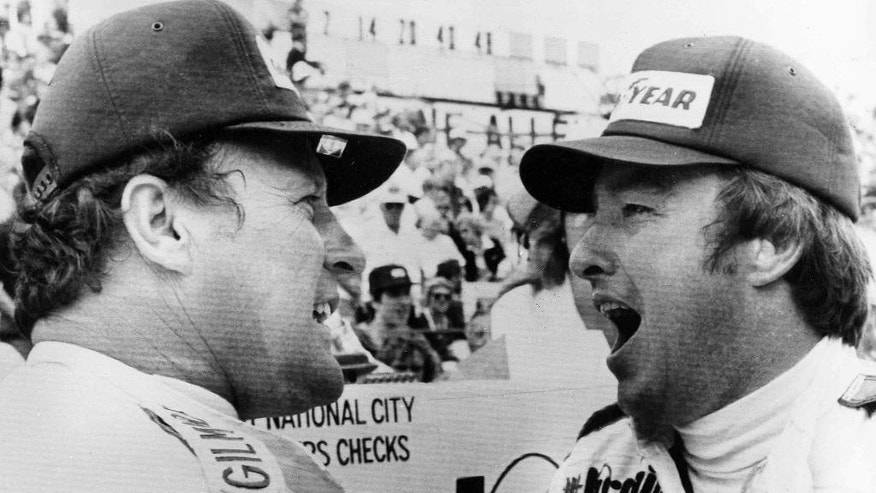 """FILE - In this May 31, 1976, file photo, Johnny Rutherford, right, and A.J. Foyt chat during a rain delay in the Indianapolis 500 auto race, in Indianapolis, Ind. Rutherford was later declared the winner when the rain continued and it became apparent the race could not be resumed. A.J. Foyt was second. In the lead-up to the 100th running of the """"The Greatest Spectacle in Racing,"""" The Associated Press interviewed the 27 living race winners on topics ranging from the best driver to greatest tradition. When it came time to name the greatest rivalry, Foyt, Mario Andretti and Bobby Unser received the most attention.  (AP Photo/File)"""