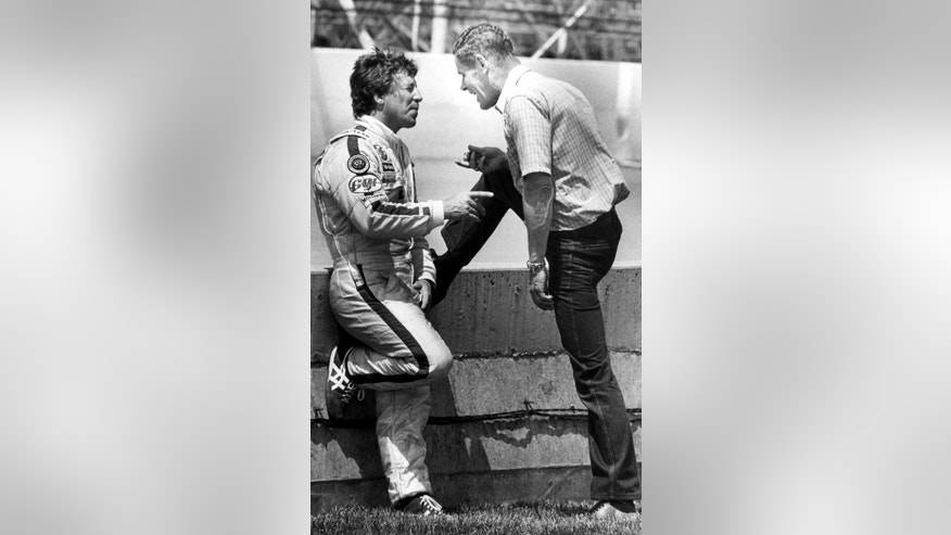 FILE - In this May 11, 1982, file photo, 1981 Indy 500 winner Bobby Unser, right, talks with 1969 winner Mario Andretti at the pit wall during practice at the Indianapolis Motor Speedway in Indianapolis on Monday, May 11, 1982. Unser was given a one lap penalty the day after taking the checkered flag last year for passing several cars under a yellow light and Andretti was named winner of the race. Following a lengthy appeal process Unser regained the title, his third Indy win. (AP Photo/File)