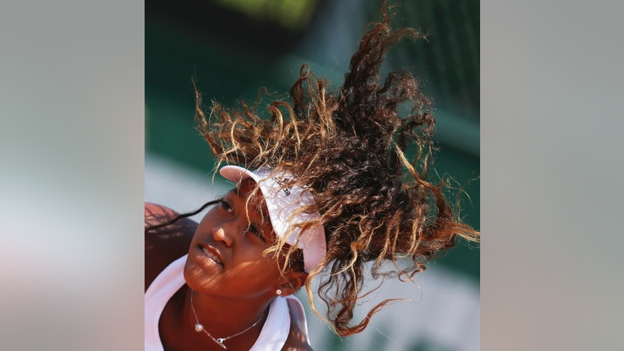 Japan's Naomi Osaka's hair flies as she serves in her second round match of the French Open tennis tournament against Croatia's Mirjana Lucic-Baroni at the Roland Garros stadium in Paris, France, Wednesday, May 25, 2016. (AP Photo/David Vincent)