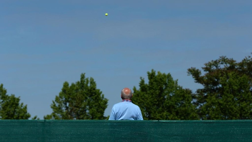 A spectator watches a tennis match during the French Open tennis tournament at the Roland Garros stadium, Wednesday, May 25, 2016 in Paris.  (AP Photo/David Vincent)