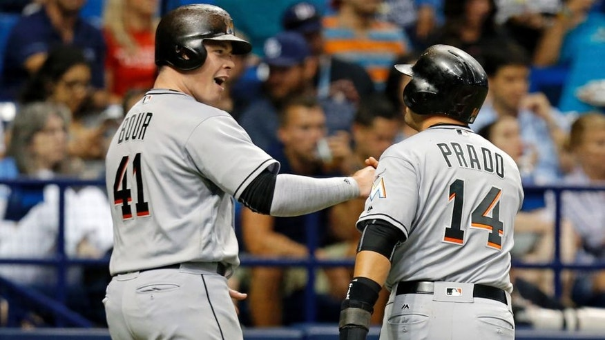 <p>Miami Marlins' Justin Bour and Martin Prado celebrate after they scored on a single by Marcell Ozuna during the third inning of a baseball game against the Tampa Bay Rays on Wednesday, May 25, 2016, in St. Petersburg, Fla. (AP Photo/Mike Carlson)</p>