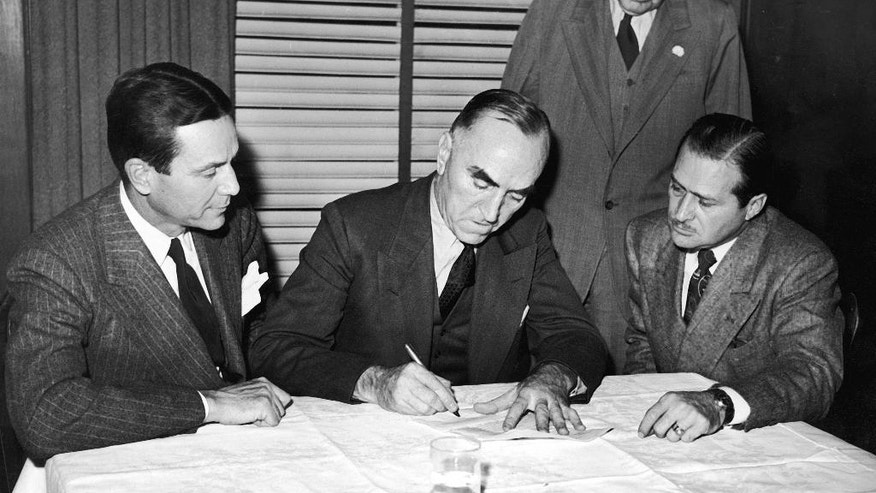 "FILE - In this Nov. 14, 1945, file photo, Capt. Eddie Rickenbacker, center, signs papers selling the Indianapolis Motor Speedway to Anton ""Tony"" Hulman Jr., left as Wilbur Shaw, right, and T.E. Myers look on in Indianapolis. In the lead-up to the 100th running of the ""The Greatest Spectacle in Racing,"" The Associated Press interviewed the 27 living race winners on topics ranging from the best driver to greatest tradition.  When asked for the most important non-driver to the Indianapolis 500, Hulman edged team owner Roger Penske in voting among the living winners. (AP Photo/File)"