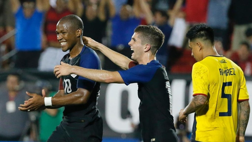 CORRECTS TO DARLINGTON NAGBE, INSTEAD OF NAGBE DARLINGTON - United States' Darlington Nagbe (10) and Christian Pulisic, center, celebrate Nagbe's goal in front of Ecuador's Cristian Ramirez (5) during the second half of an exhibition soccer match, Wednesday, May 25, 2016, in Frisco, Texas. The United States won 1-0. (AP Photo/Tony Gutierrez)
