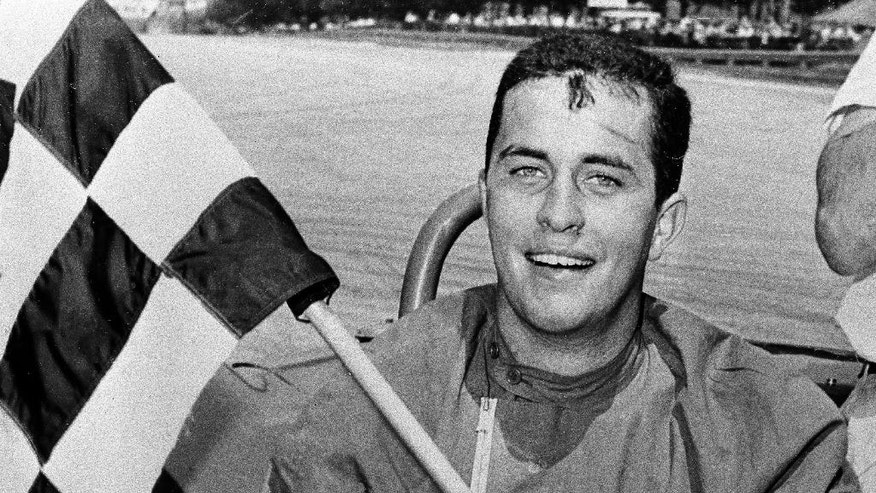 FILE - In this June 19, 1961, file photo, Roger S. Penske displays the checkered flag after he won the 100-mile race in the June sprints of Road America in Elkhart Lake, Wisc. With all the hoopla surrounding the 100th Indianapolis 500, Roger Penske has a celebration of his own going — the 50th anniversary of Team Penske.  (AP Photo/File)