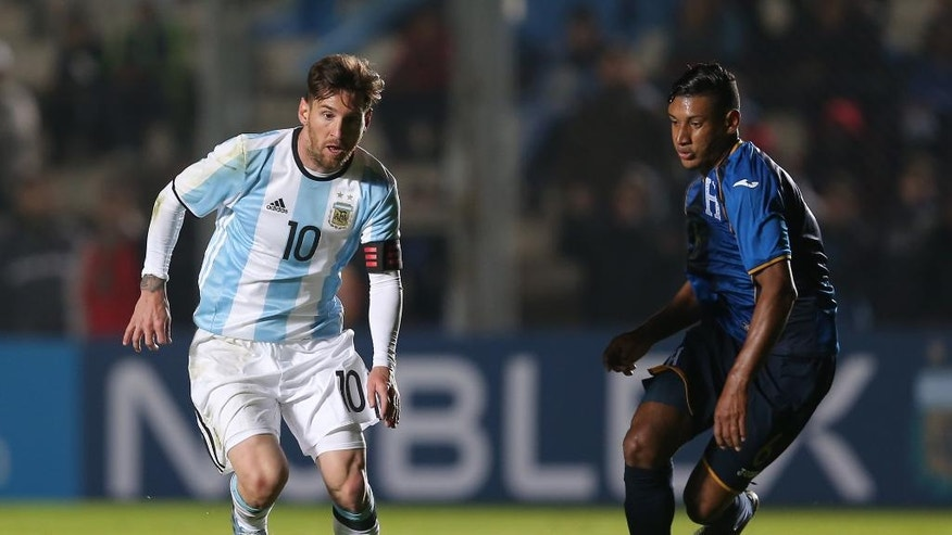 Argentina's Lionel Messi, left, fights for the ball with  Honduras' Bryan Acosta during a friendly soccer match in San Juan, Argentina, Friday, May 27, 2016. (AP Photo/Nicolas Aguilera)