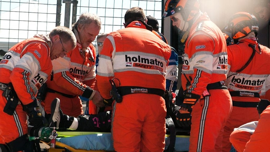 "FILE - In this Oct. 6, 2013, file photo, safety team members load driver Dario Franchitti, of Scotland, into an ambulance after a crash during the second IndyCar Grand Prix of Houston auto race, in Houston. Franchitti doesn't remember the crash that ended his career three years ago in Houston. What he does recall is that the first voice he heard afterward instantly put him at ease. ""Trammell is that you?"" Franchitti said, referring to IndyCar's safety consultant Dr. Terry Trammell. (AP Photo/Juan DeLeon, File)"