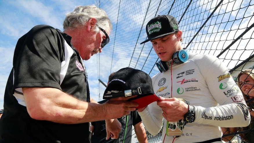 Sage Karam signs an autograph for a fan during the final practice session for the Indianapolis 500 auto race at Indianapolis Motor Speedway in Indianapolis, Friday, May 27, 2016. (AP Photo/R Brent Smith)
