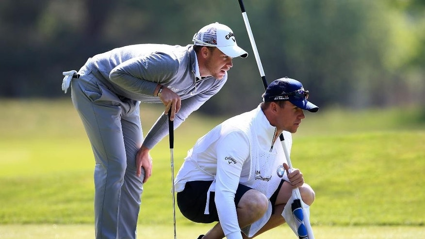 England's Danny Willett , left, lines up a putt with his caddie during the second round of the BMW PGA Championship at Wentworth golf club, Virginia Water, England, Friday May 27, 2016. (John Walton/PA via AP) UNITED KINGDOM OUT