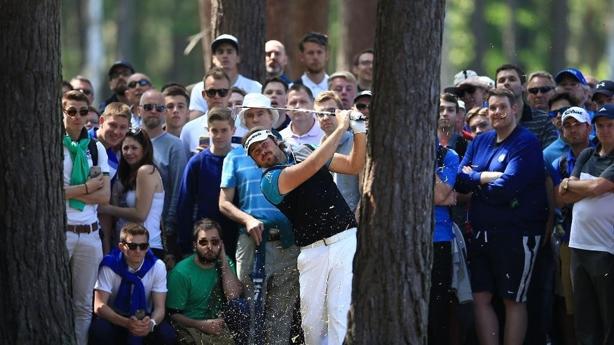 France's Victor Dubuisson plays a shot from between two trees during the second round of the BMW PGA Championship at Wentworth golf club, Virginia Water, England, Friday May 27, 2016. (John Walton/PA via AP) UNITED KINGDOM OUT