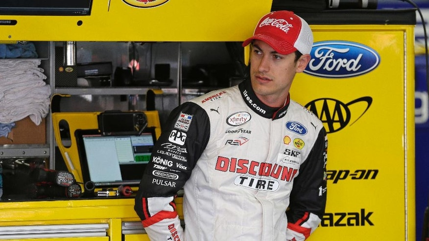 Joey Logano looks from the garage before practice for Sunday's NASCAR Sprint Cup series auto race at Charlotte Motor Speedway in Concord, N.C., Saturday, May 28, 2016. (AP Photo/Chuck Burton)