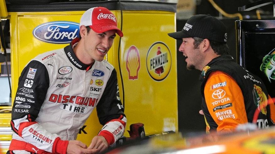 Joey Logano, left, talks with Martin Truex Jr, right, before practice for Sunday's NASCAR Sprint Cup series auto race at Charlotte Motor Speedway in Concord, N.C., Saturday, May 28, 2016. (AP Photo/Chuck Burton)