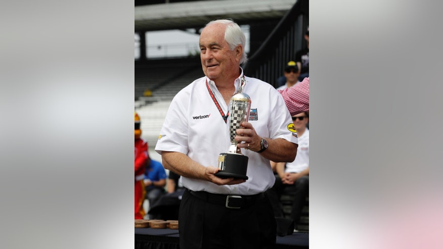 "Car owner Roger Penske displays the ""Baby"" Borg-Warner Trophy presents to the wining car owner of last years race during the drivers meeting for the Indianapolis 500 auto race at Indianapolis Motor Speedway in Indianapolis, Saturday, May 28, 2016. (AP Photo/Darron Cummings)"