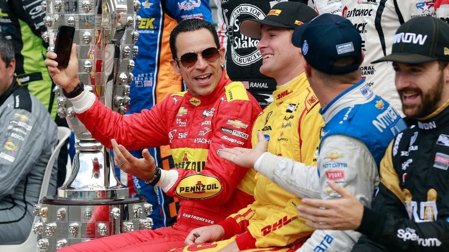 Helio Castroneves, left, jokes with Ryan Hunter-Reay, center, and Tony Kanaan during a photo of the starting field before the final practice session for the Indianapolis 500 auto race at Indianapolis Motor Speedway in Indianapolis, Friday, May 27, 2016.
