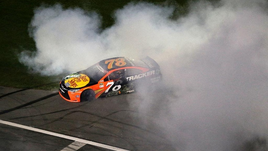 Martin Truex Jr. (78) does a burnout after winning the NASCAR Sprint Cup Series auto race at the Charlotte Motor Speedway in Concord, N.C., Sunday, May 29, 2016. (AP Photo/Gerry Broome)