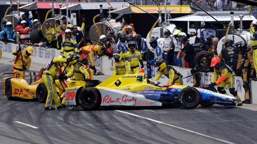The crews of Townsend Bell (29) and Ryan Hunter-Reay move their cars back to their pits following a collision in the pit area during the 100th running of the Indianapolis 500 auto race at Indianapolis Motor Speedway in Indianapolis, Sunday, May 29, 2016. (AP Photo/R Brent Smith)