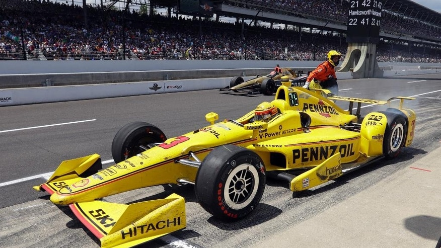 Helio Castroneves, of Brazil, returns to the track after a pit stop during the 100th running of the Indianapolis 500 auto race at Indianapolis Motor Speedway in Indianapolis, Sunday, May 29, 2016. (AP Photo/Darron Cummings)