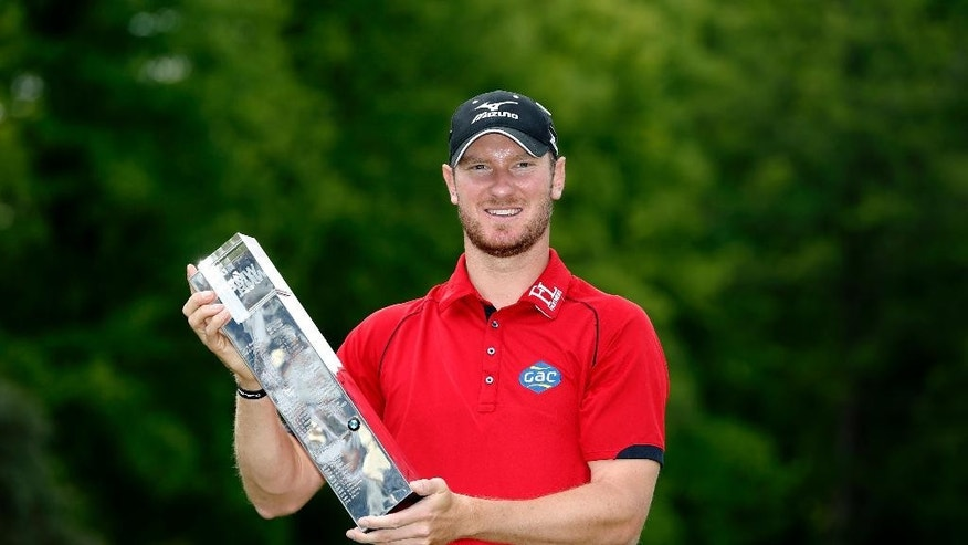 England's Chris Wood celebrates with the trophy after winning the PGA Championship at Wentworth Club, in Virginia Water, England, Sunday May 29, 2016.  Wood shot a front-nine 29 before overcoming a late run of bogeys to win the PGA Championship by one stroke for the biggest victory of his career on Sunday. (Steve Paston / PA via AP) UNITED KINGDOM OUT - NO SALES - NO ARCHIVES