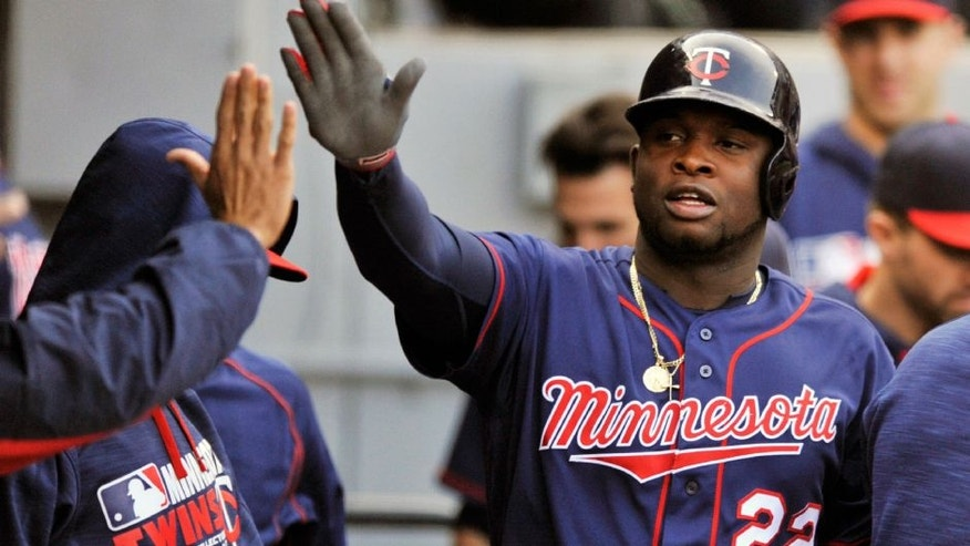 Minnesota Twins' Miguel Sano celebrates with teammates in the dugout after scoring on a Oswaldo Arcia walk during the first inning of a baseball game against the Chicago White Sox.
