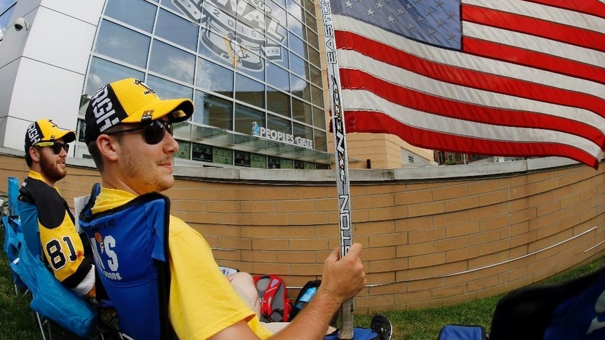 Nick Comito, foreground, and Mitch Bell, left, both of Greensburg, Pa., wave the American Flag on Memorial Day as they wait outside the Consol Energy Center for Game 1 of the Stanley Cup final series between the San Jose Sharks and the Pittsburgh Penguins Monday, May 30, 2016, in Pittsburgh. (AP Photo/Gene J. Puskar)
