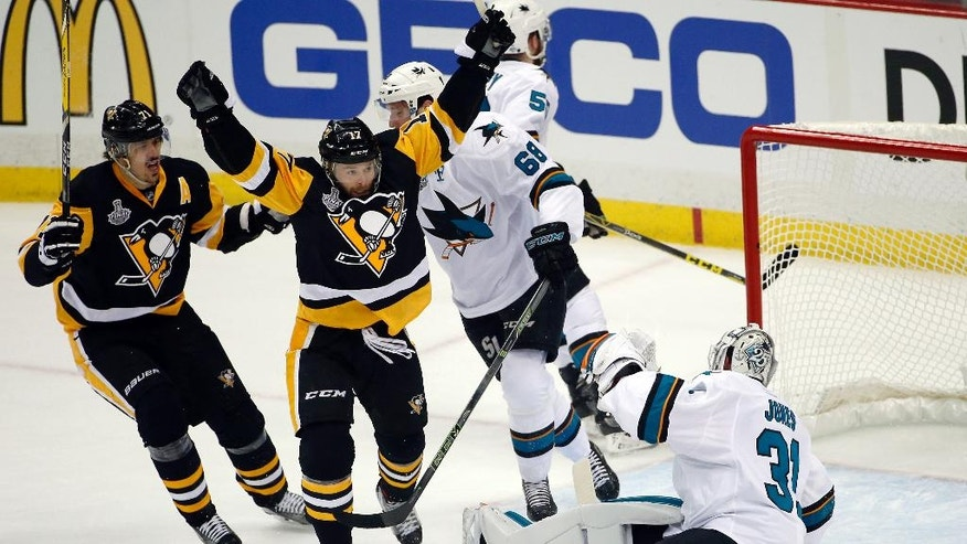 Pittsburgh Penguins' Bryan Rust, center, celebrates his goal against San Jose Sharks goalie Martin Jones (31) during the first period in Game 1 of the Stanley Cup final series Monday, May 30, 2016, in Pittsburgh. (AP Photo/Gene J. Puskar)
