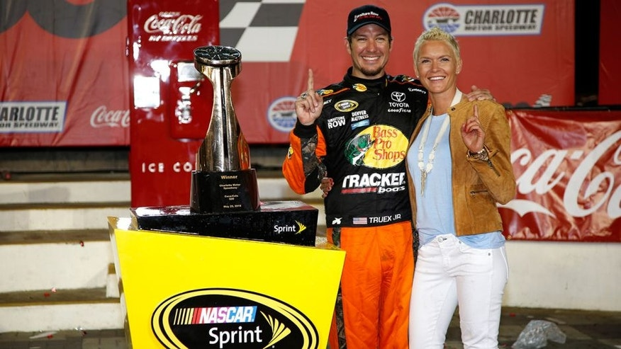 CHARLOTTE, NC - MAY 29: Martin Truex Jr., driver of the #78 Bass Pro Shops/Tracker Toyota, and his girlfriend Sherry Pollex pose with the trophy in Victory Lane after winning the NASCAR Sprint Cup Series Coca-Cola 600 at Charlotte Motor Speedway on May 29, 2016 in Charlotte, North Carolina. (Photo by Todd Warshaw/NASCAR via Getty Images)