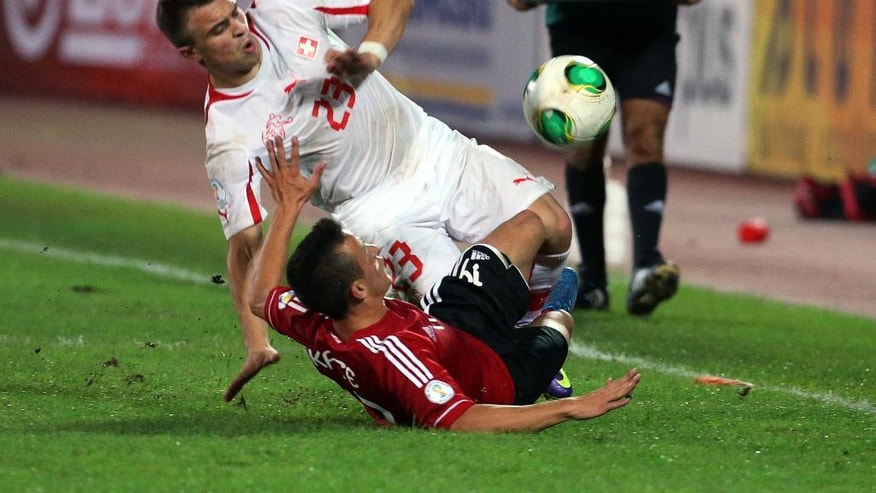 FILE - In this Friday Oct. 11, 2013, file photo, Albania's Ergys Kace, bottom, fights for the ball with Switzerland's Xherdan Shaqiri, during their World Cup Group E qualifier soccer match in Tirana, Albania. The European Championship has a reputation for being the soccer fans' favorite tournament on the global calendar. (AP Photo/Hektor Pustina, File)