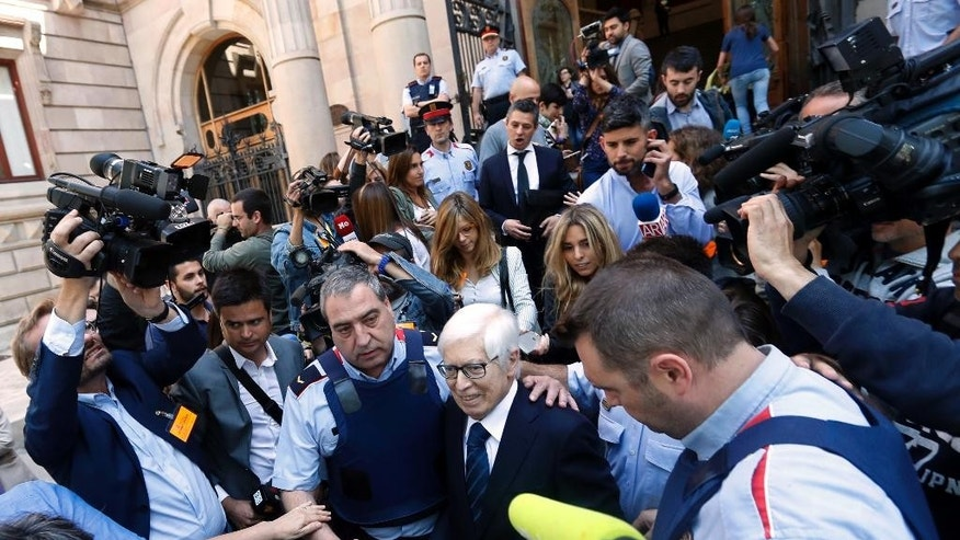 Lionel Messi's lawyer Enrique Bacigalupo, center right, is surrounded by journalists on leaving a court in Barcelona, Spain, Tuesday May 31, 2016. Lionel Messi's tax trial began Tuesday with the player deciding not to appear in court for early proceedings. Messi is facing a prison sentence of nearly two years on charges he failed to properly pay taxes for part of his earnings from Barcelona from 2007-09. (AP Photo/Manu Fernandez)