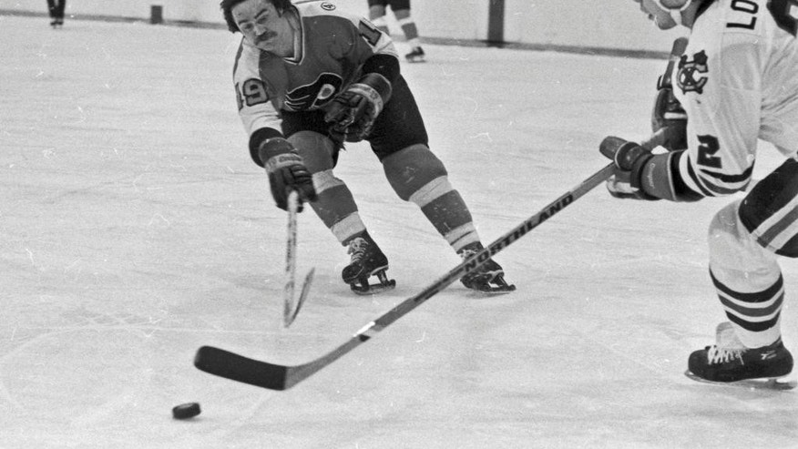 FILE- In this Feb. 1, 1978, file photo, Philadelphia Flyer' Rick MacLeish, left, stretches to keep the puck away from Chicago Blackhawks' Dave Logan during an NHL hockey game in Chicago. MacLeish, who starred for the Broad Street Bullies teams of the Flyers that won the Stanley Cup in 1974 and 1975, has died, the team announced Tuesday, May 31, 2016. He was 66.  (AP Photo/Fred Jewell, File)