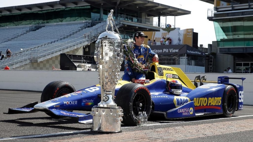 Indianapolis 500 champion Alexander Rossi poses with the Borg-Warner Trophy during the traditional winners photo on the start/finish line at Indianapolis Motor Speedway in Indianapolis, Monday, May 30, 2016. Rossi won the 100th running of the Indianapolis 500 auto race on Sunday. (AP Photo/Michael Conroy)