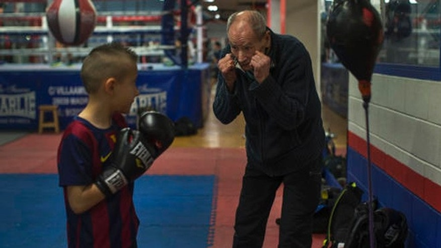 In this Monday, April 25, 2016 photo, boxing coach Manolo del Rio, right, talks to his young pupil Mario Andres Ciobanu, 8, during a training session at El Rayo boxing gym in Madrid, Spain. At 84, Manolo del Rio is something of a legend in Spanish boxing circles, having spent more than 65 years training some of the country's best fighters and pledging to keep on going until he drops. (AP Photo/Francisco Seco)