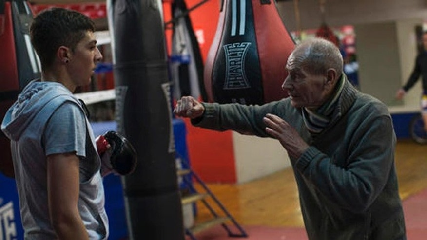In this Friday, April 22, 2016 photo, boxing coach Manolo del Rio, right, talks to one of his pupils during a training session at El Rayo boxing gym in Madrid, Spain.  At 84, Manolo del Rio is something of a legend in Spanish boxing circles, having spent more than 65 years training some of the country's best fighters and pledging to keep on going until he drops, he spends 12-14 hours a day at the gym in a working class neighborhood of Madrid. (AP Photo/Francisco Seco)