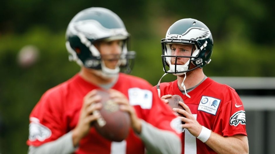 Philadelphia Eagles quarterbacks Sam Bradford, left, and Carson Wentz prepare to throw passes at the team's NFL football training facility, Tuesday, May 17, 2016, in Philadelphia. (AP Photo/Matt Rourke)