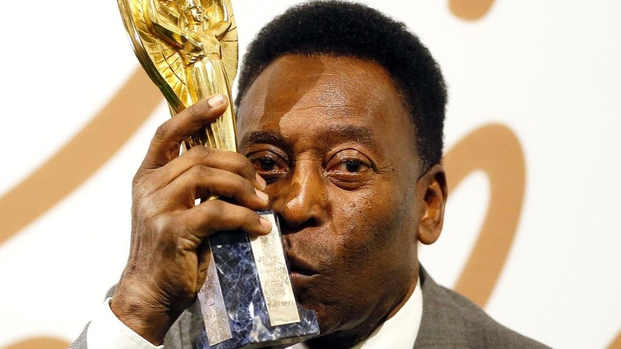 Brazilian former footballer Pele holds up his copy of the Jules Rimet Trophy, during a media opportunity in London, Wednesday, June 1, 2016. The three-time World Cup Champion, FIFA Player of the Century and Brazilian Football icon, will offer his vast collection of memorabilia, awards, personal property and iconic items from his entire career, to be auctioned on June 7, 8 and 9 in London. (AP Photo/Kirsty Wigglesworth)