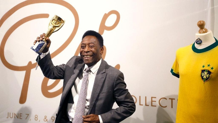 Pele,  former Brazilian soccer star holds up his copy of the Jules Rimet Trophy, during a media opportunity in London, Wednesday, June 1, 2016. The three-time World Cup Champion, FIFA Player of the Century and Brazilian Football icon, will offer his vast collection of memorabilia, awards, personal property and iconic items from his entire career, to be auctioned on June 7, 8 and 9 in London. (AP Photo/Kirsty Wigglesworth)