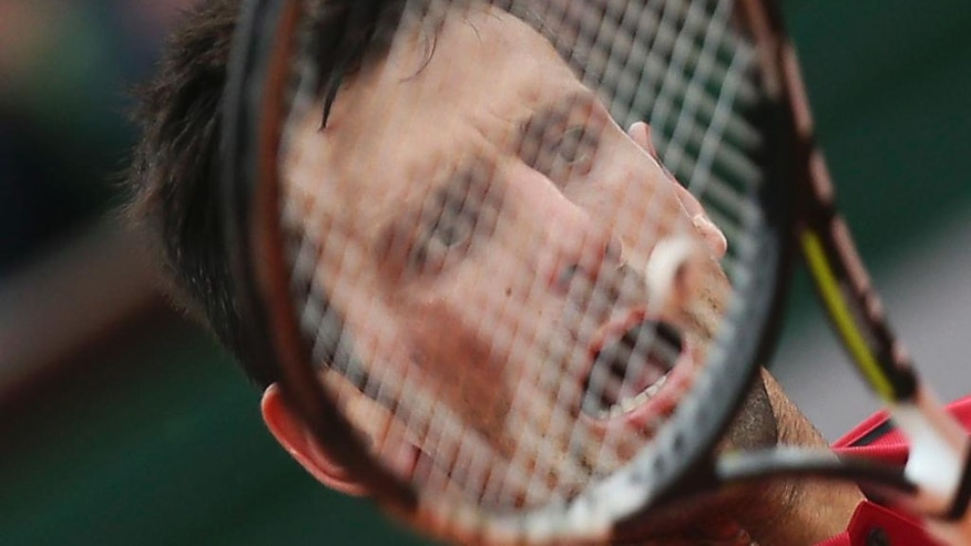 Serbia's Novak Djokovic returns the ball in the fourth round match of the French Open tennis tournament against Spain's Roberto Bautista Agut at the Roland Garros stadium in Paris, France, Wednesday, June 1, 2016. (AP Photo/David Vincent)