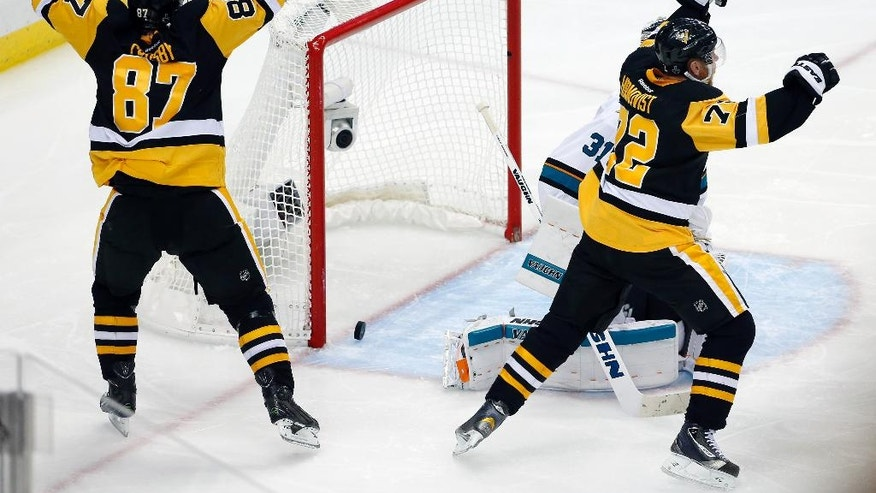 Pittsburgh Penguins' Sidney Crosby (87) and Patric Hornqvist, right, celebrate a goal by Conor Sheary against San Jose Sharks goalie Martin Jones (31) during overtime in Game 2 of the NHL hockey Stanley Cup Finals on Wednesday, June 1, 2016, in Pittsburgh. The Penguins won 2-1 to take a 2-0 lead in the series. (AP Photo/Gene J. Puskar)