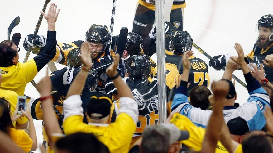 Pittsburgh Penguins' Conor Sheary is covered as he is mobbed by teammates after his goal against the San Jose Sharks during overtime in Game 2 of the NHL hockey Stanley Cup Finals on Wednesday, June 1, 2016, in Pittsburgh. The Penguins won 2-1 and lead the series 2-0. (AP Photo/Gene J. Puskar)