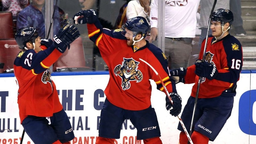 Mar 31, 2016; Sunrise, FL, USA; Florida Panthers center Jonathan Huberdeau (11) celebrates his goal against the New Jersey Devils with right wing Shawn Thornton (22) and center Aleksander Barkov (16) in the second period at BB&T Center. Mandatory Credit: Robert Mayer-USA TODAY Sports