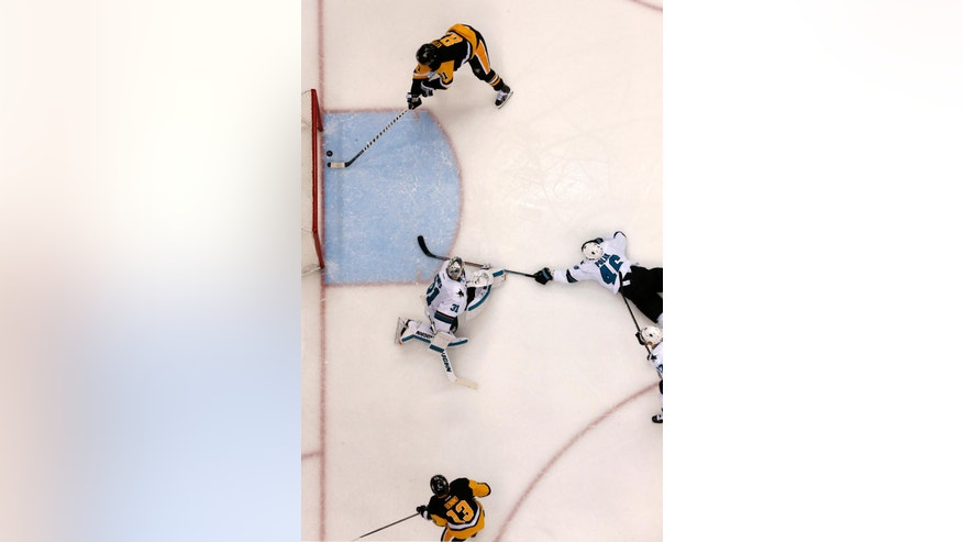 Pittsburgh Penguins' Phil Kessel (81) takes a pass from teammate Nick Bonino (13) and backhands it into the net for a goal behind San Jose Sharks goalie Martin Jones (31) and defenseman Roman Polak (46) during the second period of Game 2 of the NHL hockey Stanley Cup Finals on Wednesday, June 1, 2016 in Pittsburgh. The Penguins won 2-1. (AP Photo/Gene J. Puskar)