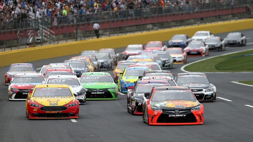 CHARLOTTE, NC - MAY 29: Martin Truex Jr., driver of the #78 Bass Pro Shops/Tracker Toyota, and Joey Logano, driver of the #22 Shell Pennzoil Ford, lead a pack of cars during the NASCAR Sprint Cup Series Coca-Cola 600 at Charlotte Motor Speedway on May 29, 2016 in Charlotte, North Carolina. (Photo by Jerry Markland/NASCAR via Getty Images)
