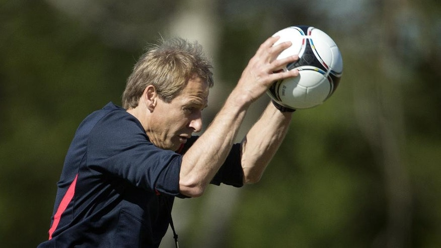 FILE - In this Feb. 4, 2013, file photo, Coach Jurgen Klinsmann slams the ball to the ground during a U.S. Men's National Team practice at the FIU Soccer Stadium, in Miami. (AP Photo/J Pat Carter, File)