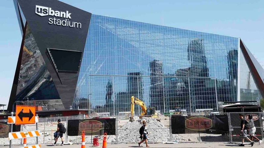 The Minneapolis skyline is reflected in the new U.S. Bank Stadium in Minneapolis as it nears completion for the $1.2 billion home of the Minnesota Vikings NFL football team beginning this season in Minneapolis. (AP Photo/Jim Mone)