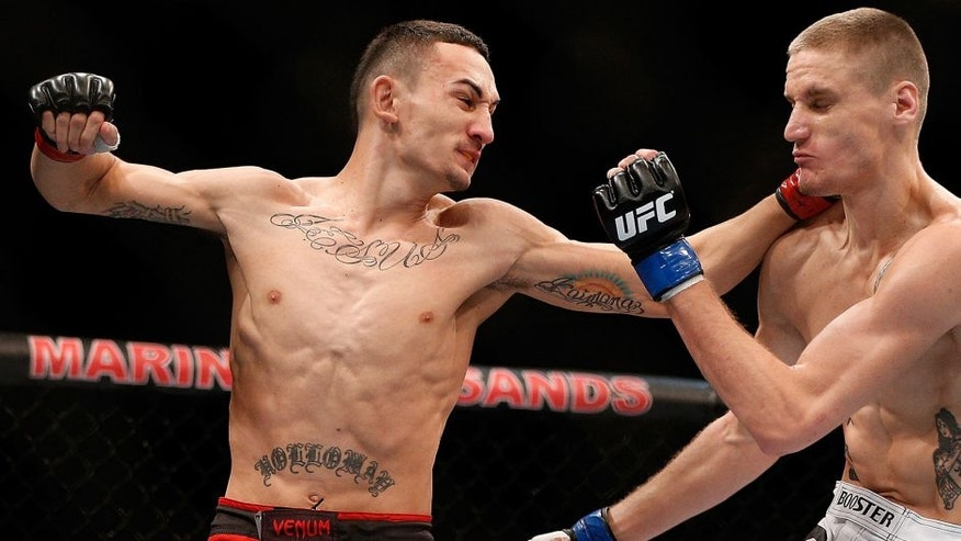 SINGAPORE - JANUARY 04: (L-R) Max Holloway punches Will Chope in their featherweight bout during the UFC Fight Night event at the Marina Bay Sands Resort on January 4, 2014 in Singapore. (Photo by Josh Hedges/Zuffa LLC/Zuffa LLC via Getty Images)